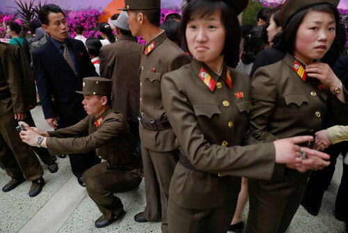 Soldiers pose for a photo during the flower exhibition marking the 105th birth anniversary of the country's founding father, Kim Il Sung in Pyongyang
