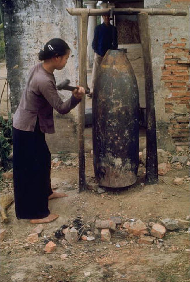 Крестьянка стучит по снарядной гильзе, используемой в качестве сигнала воздушной тревоги