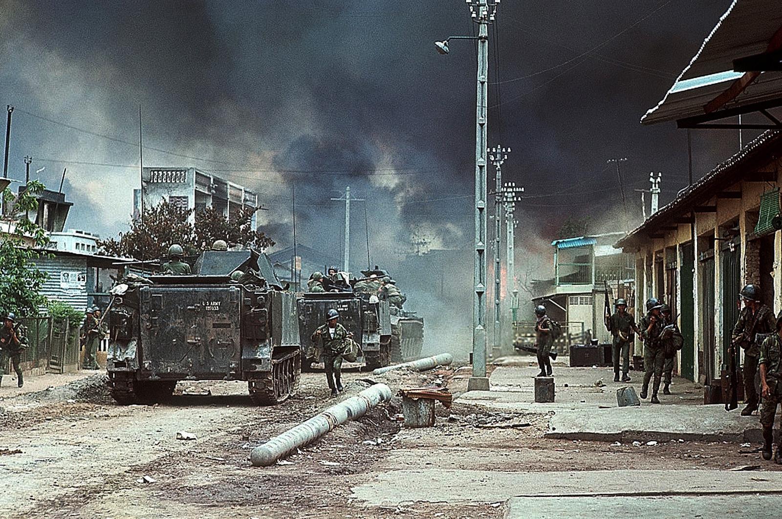 Войска передвигаются в пешем порядке и на машинах по улице в северном Сайгоне, окутанном дымом от ожесточенных боев во время наступления Вьетконга. 6 мая