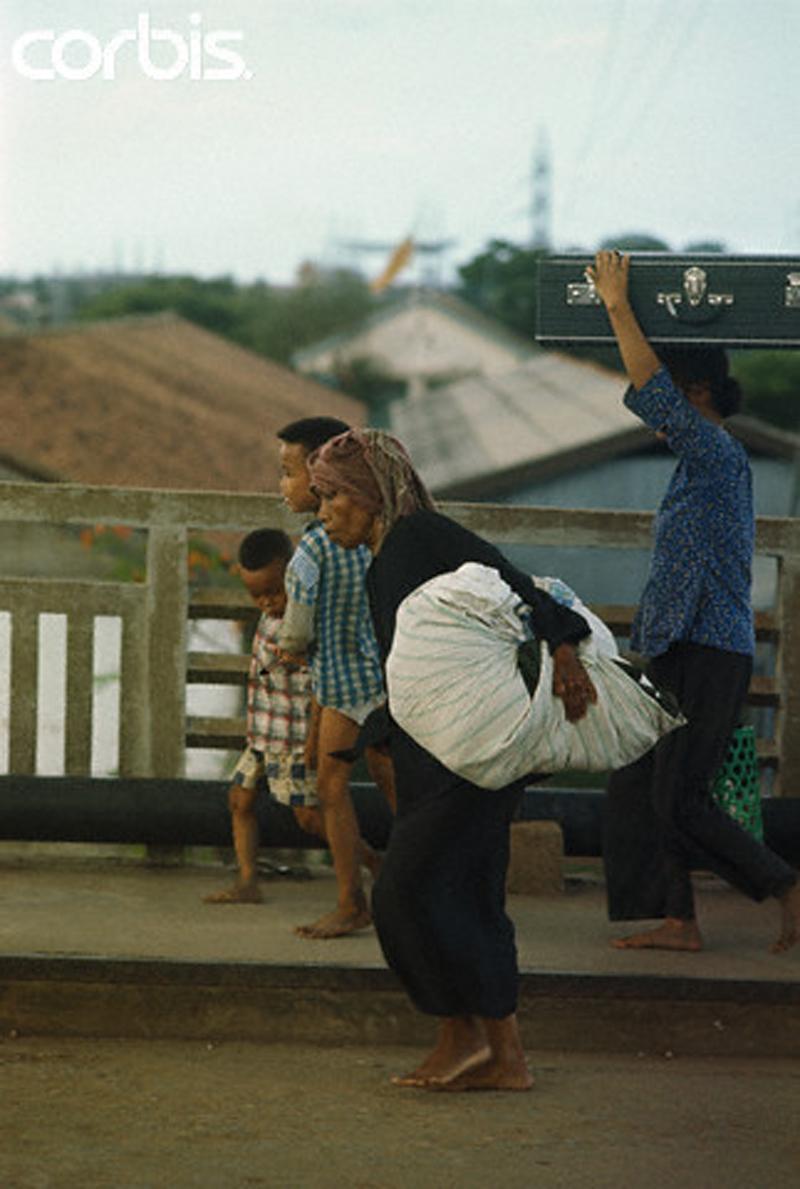 Беженцы пытаются спасти свои вещи во время бегства из Тёлона. 5 мая