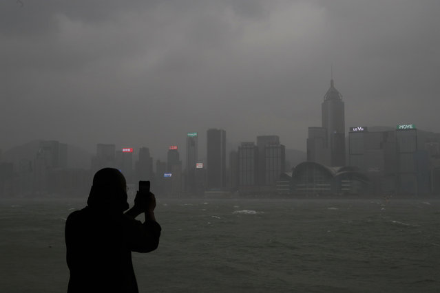 A woman takes pictures on the waterfront of Victoria Harbour as Typhoon Haima approaches Hong Kong,