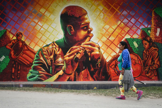 A woman walks past a mural in Toribio, department of Cauca, Colombia, on October 3, 2016. (Photo by