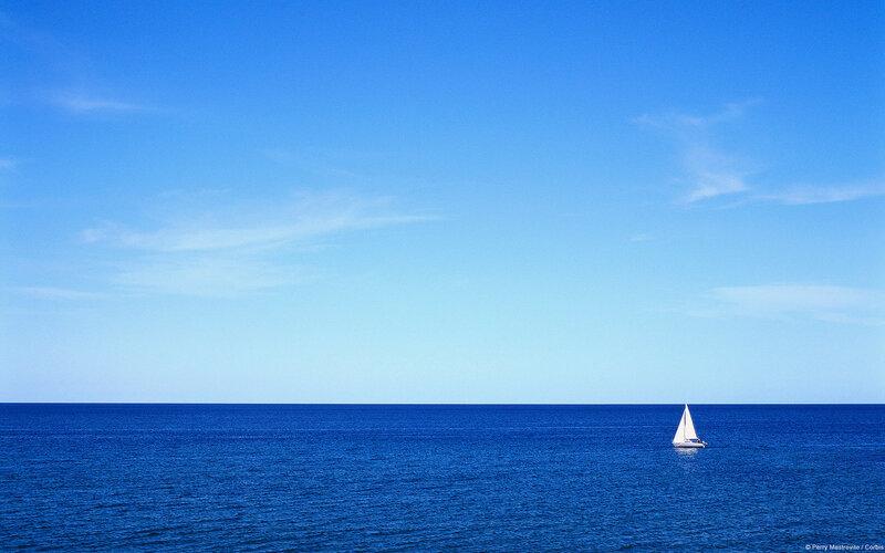 Lone sailboat in the empty ocean, Iles de la Madeleine, Quebec, Canada