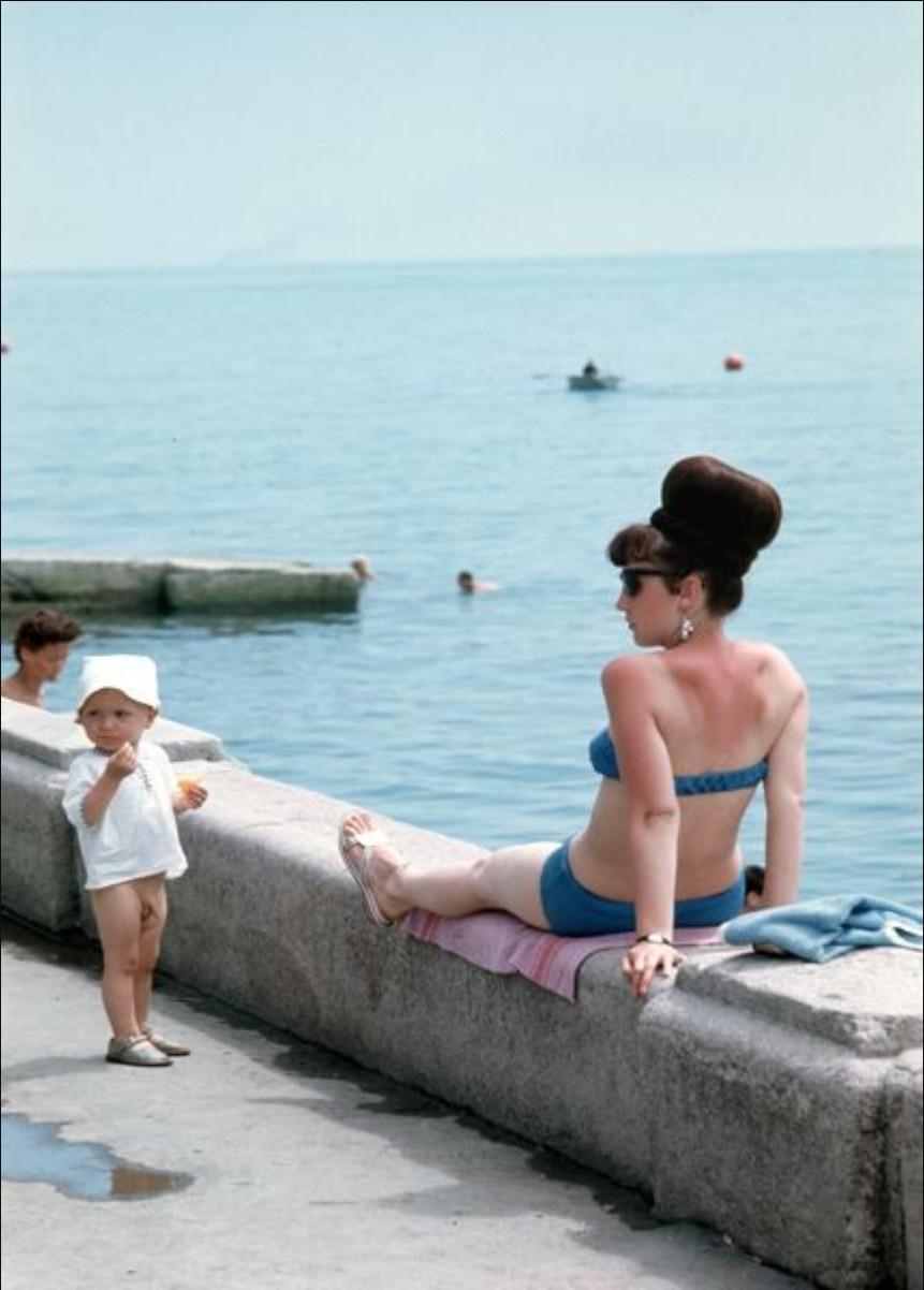 Женщина с ребенком загорает на набережной