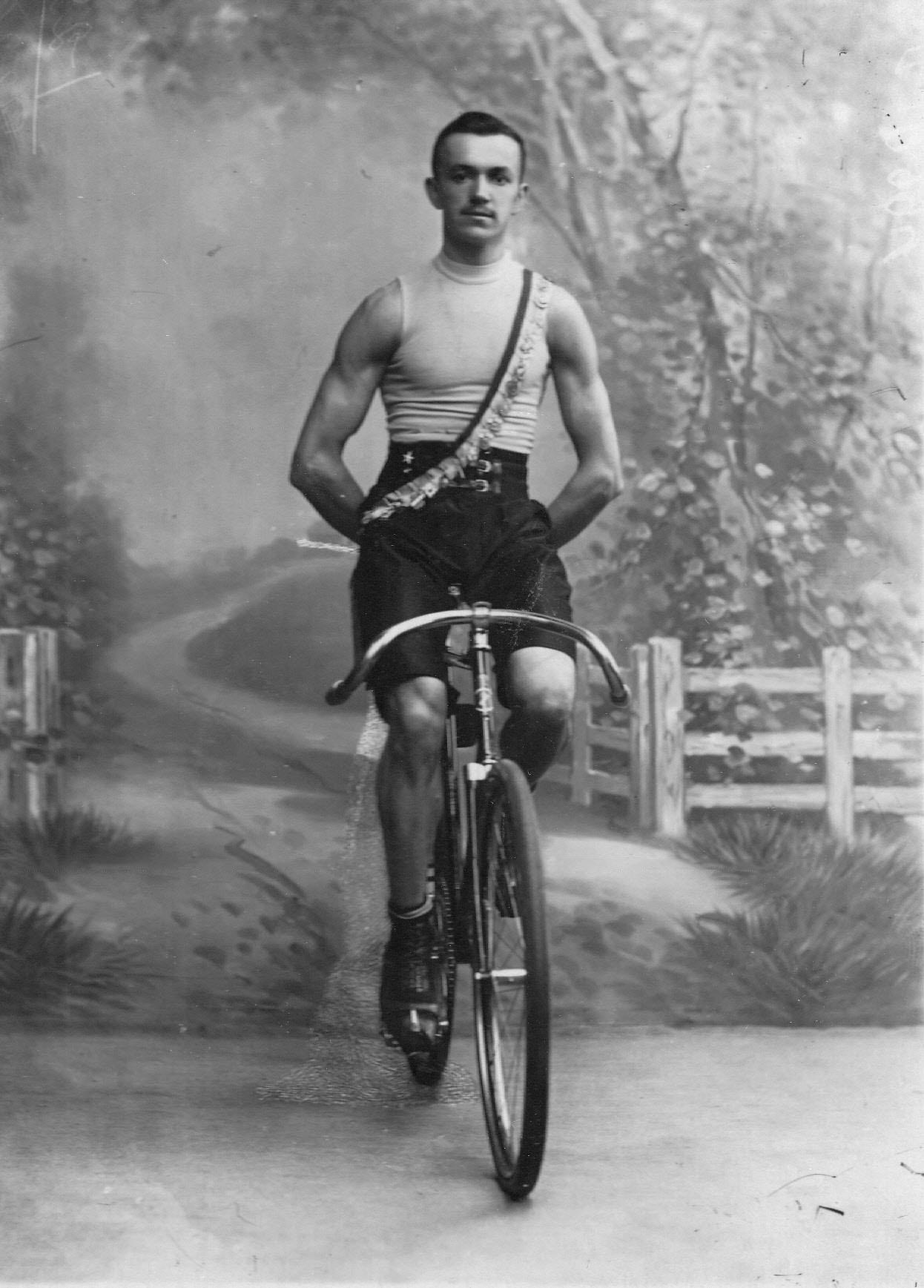 Велогонщик, победитель соревнований, на велосипеде. 1910