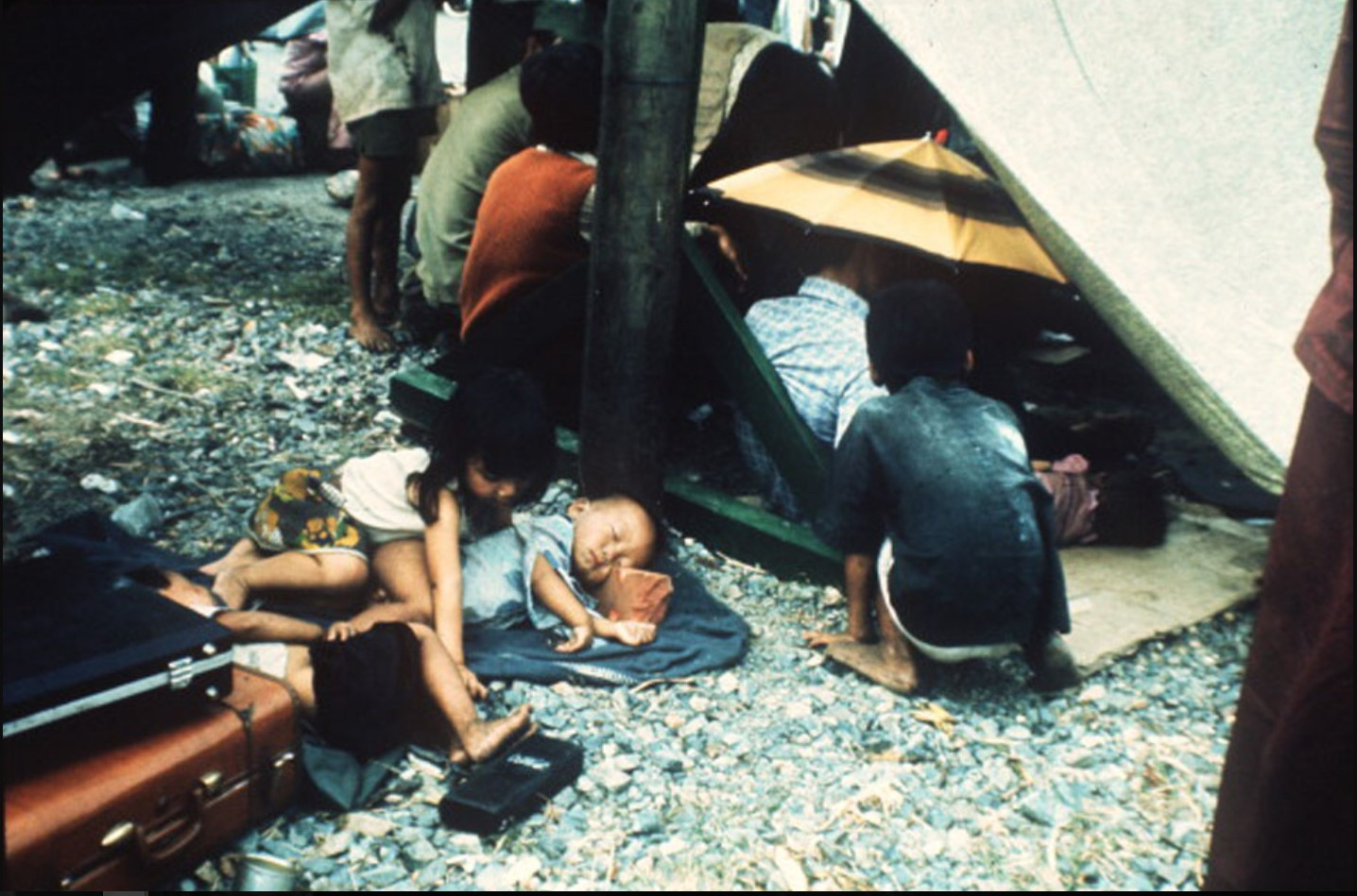 Некоторые из более чем 7000 беженцев, погрузившихся на борт южно-вьетнамского военно-морского корабля HQ-504, ждут на палубе, чтобы отправиться в порт Вунгтау, единственный портовый город под контролем правительства