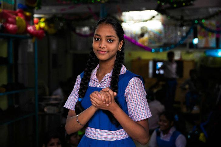 Глухонемая девушка с помощью языка жестов показывает слово «дружба». Фотограф сделала этот кадр во в