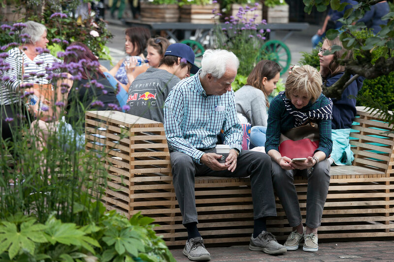 An elderly couple is sitting on a bench, looking into the phone. A small garden in the center of Covent Garden.