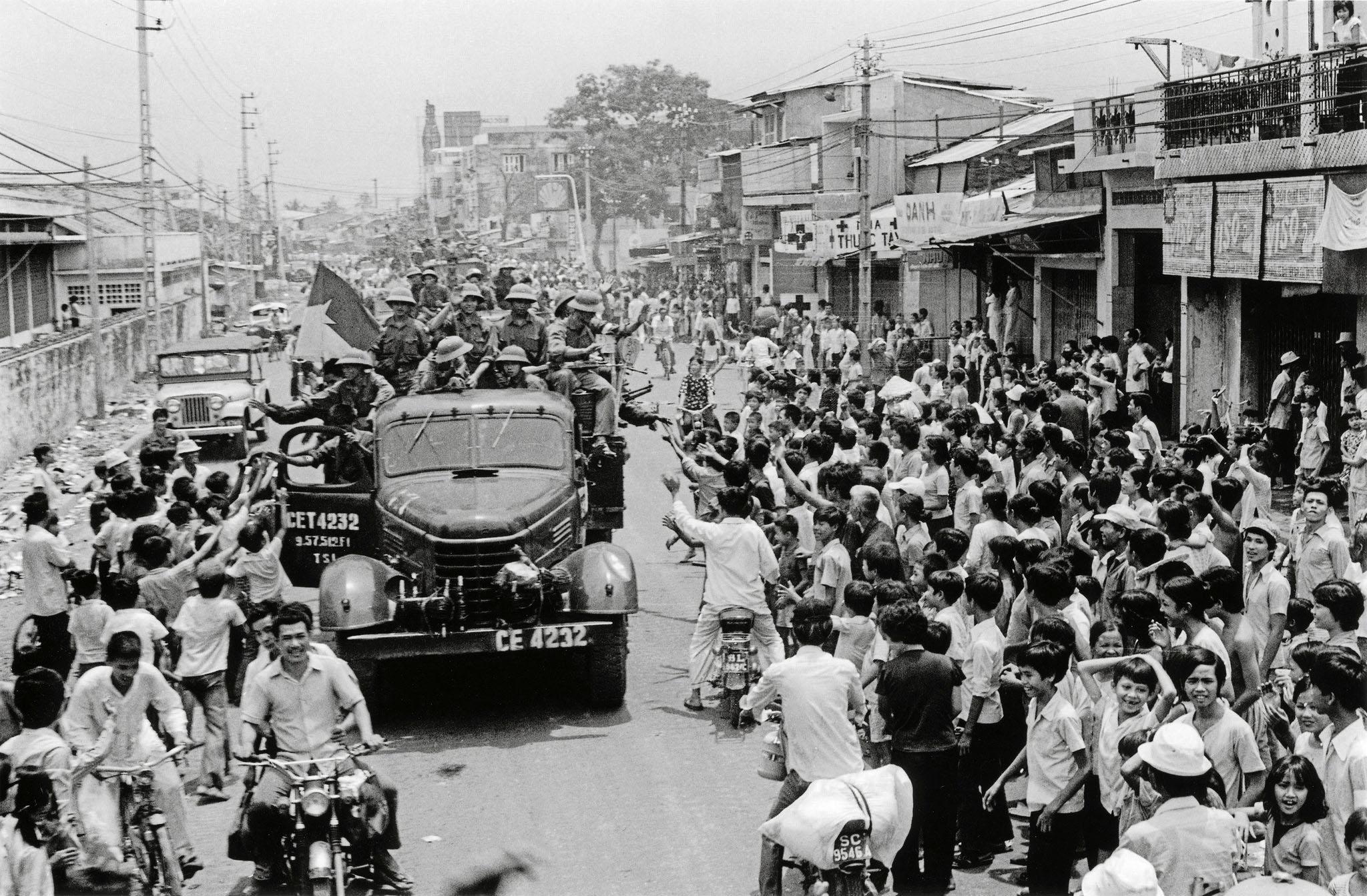 Жители Сайгона выходят на улицу, чтобы приветствовать прибытие солдат северо-вьетнамской армии на грузовиках после падения Сайгона. 30 апреля