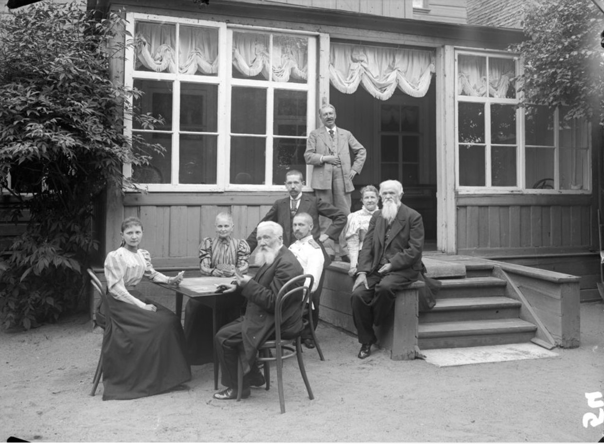 Группа людей на даче играют в карты