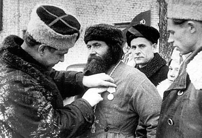 Командир 5-й Ленинградской партизанской бригады, Герой Советского Союза К.Д. Карицкий прикрепляет ме