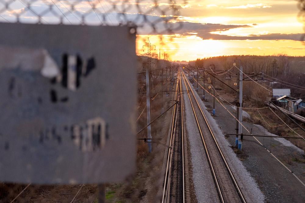 железнодорожные пути при свете заходящего солнца, табличка в разфокусе