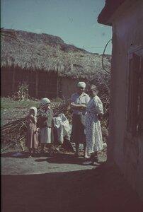 Две молодые женщины и две девочки возле дома