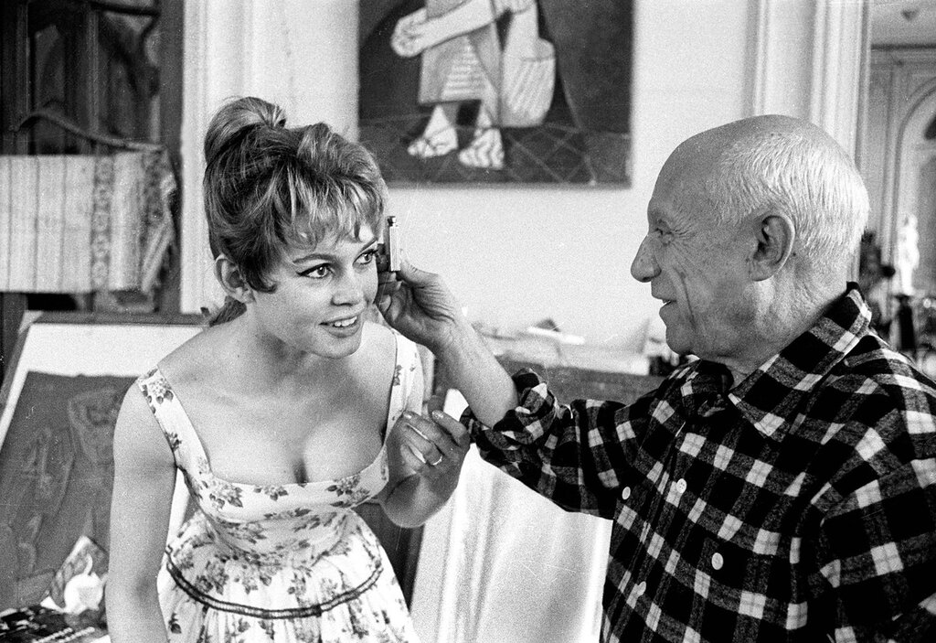 Spanish painter Pablo Picasso (1881 - 1973) checks French  actress Brigitte Bardot's face with a light meter at his studio in Vallauris, on the Cote d'Azur, during the Cannes Film Festival, April 1956 . (Photo by Jerome Brierre/RDA/Getty Images)