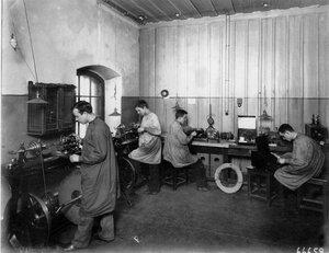 Рабочие за изготовлением деталей и за сборкой радиоаппаратуры.