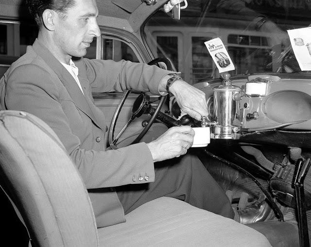 Кофеварка на панели приборов автомобиля На фотографии 1950 года водитель показывает свое изобретение