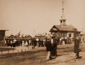 Участники церемонии открытия выставки во время молебна у модели церкви-школы.