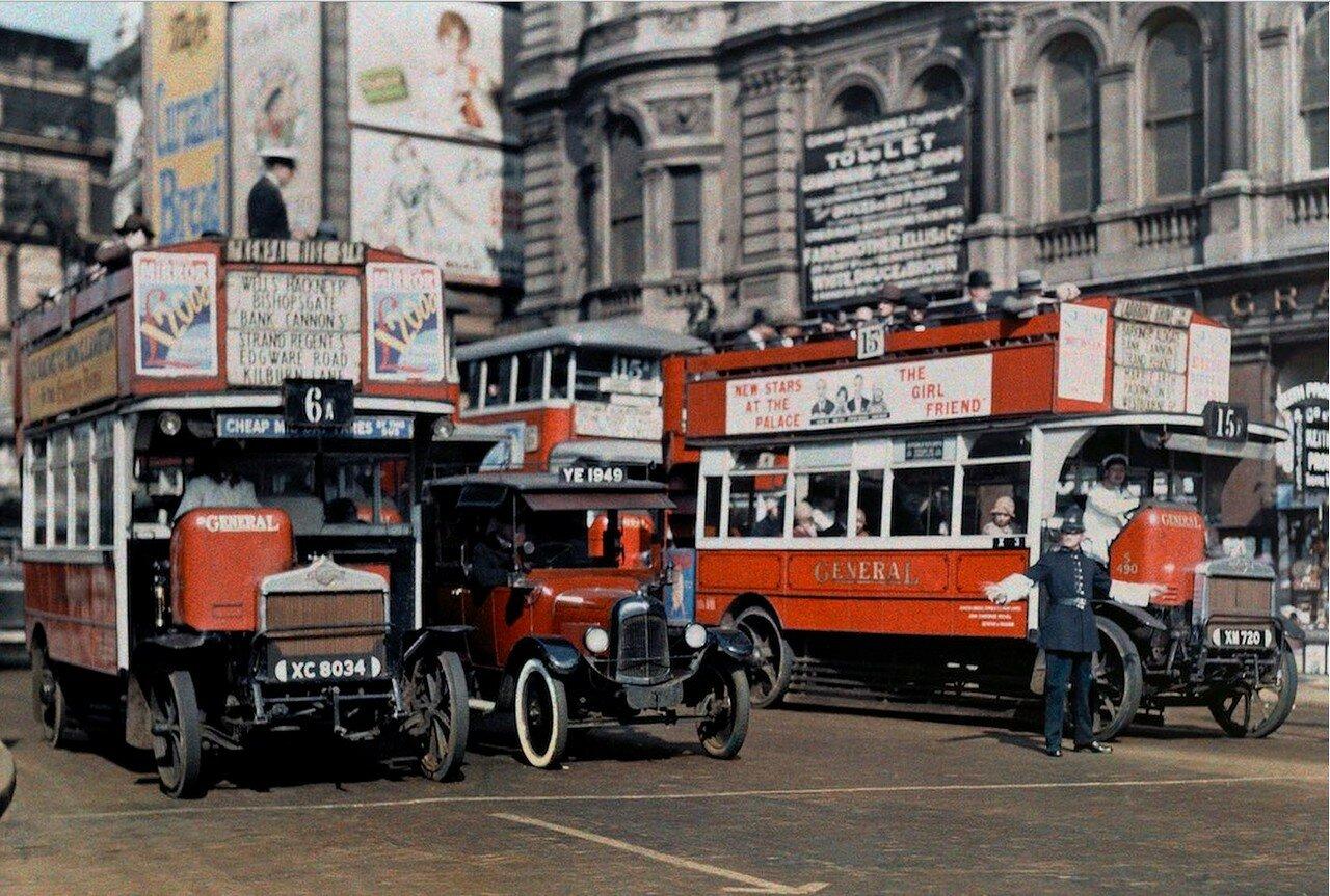 Регулировщик движения останавливает автобусы на Трафальгарской площади в Лондоне