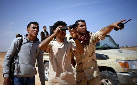 Libya Dawn fighters look at Islamic State militant positions near Sirte