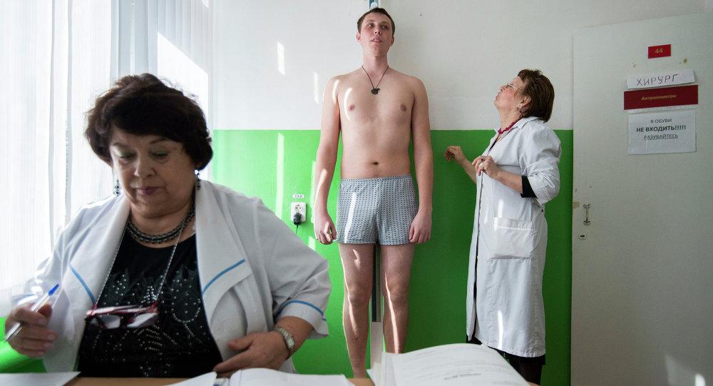 Призывник во время медосмотра у хирурга на сборном призывном пункте