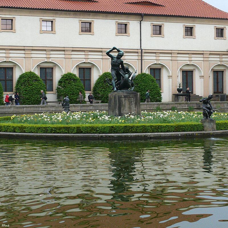 бассейн с островком, в центре - статуя геркулеса на фоне замыкающего комплекс манежа