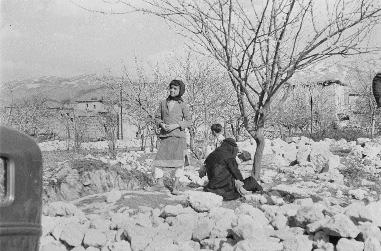 Двое детей и женщина возле руин храмового комплекса