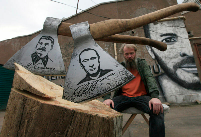 Russian artist Vasily Slonov poses for a picture with axes engraved with portraits of Russian President Vladimir Putin and Soviet leader Josef Stalin, during a presentation of his new art project