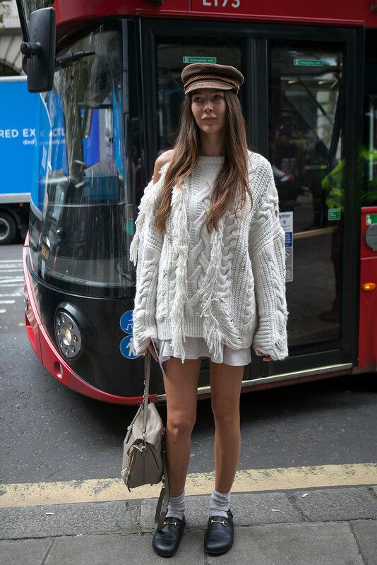 LONDON, ENGLAND - September 15, 2017 Estelle Pigault wearing a white knit, Chloe bag, slippers, socks, flat cap during London Fashion Week September 2017 outside Eudon Choi