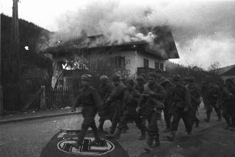 Советские солдаты проходят мимо горящего здания гестапо в окрестностях Вены.