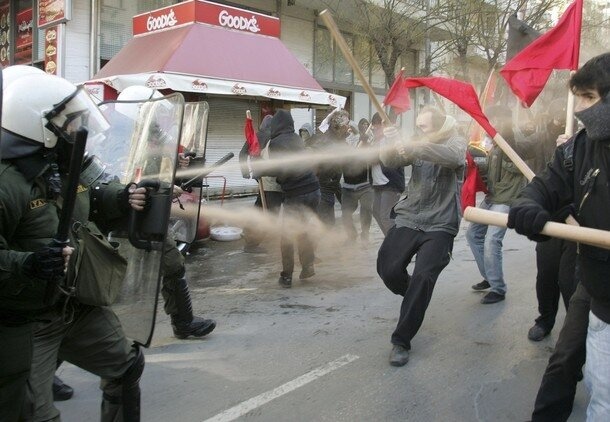 A policeman sprays tear gas at protesters during riots in Thessaloniki