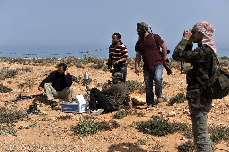 Libyan rebels stand near Nofilia, 100 ki