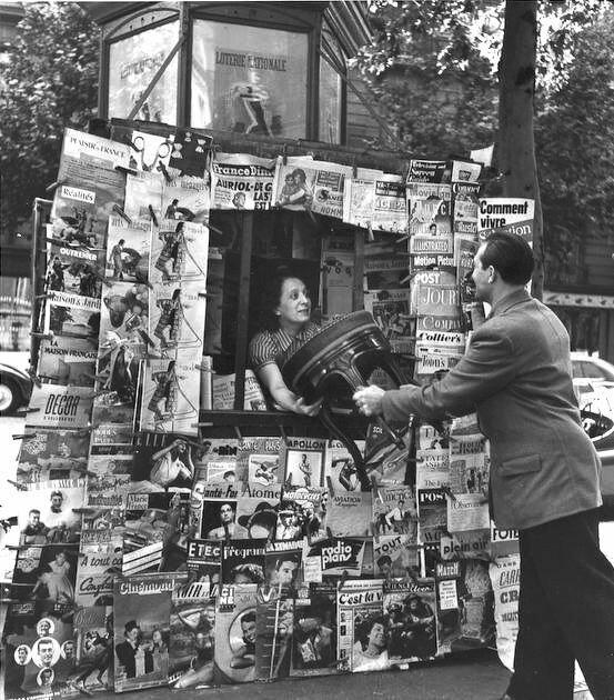 1951. Человек вручает стул женщине в газетном киоске на Елисейских Полях