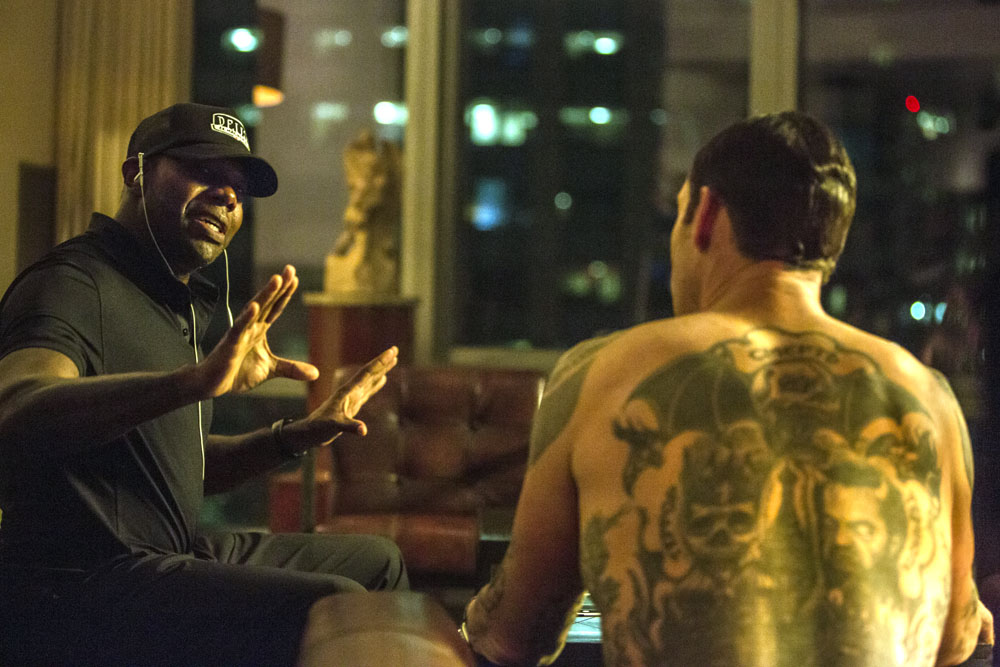 Director Antoine Fuqua (left) sits down with Marton Csokas on the set of Columbia Pictures' THE EQUALIZER.