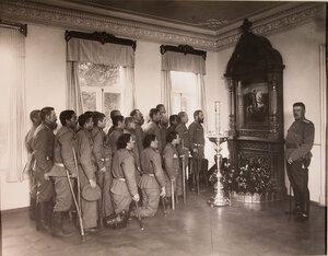 Увечные воины, призреваемые в патронате-убежище, во время молитвы у школы с изображением Георгия Победоносца.