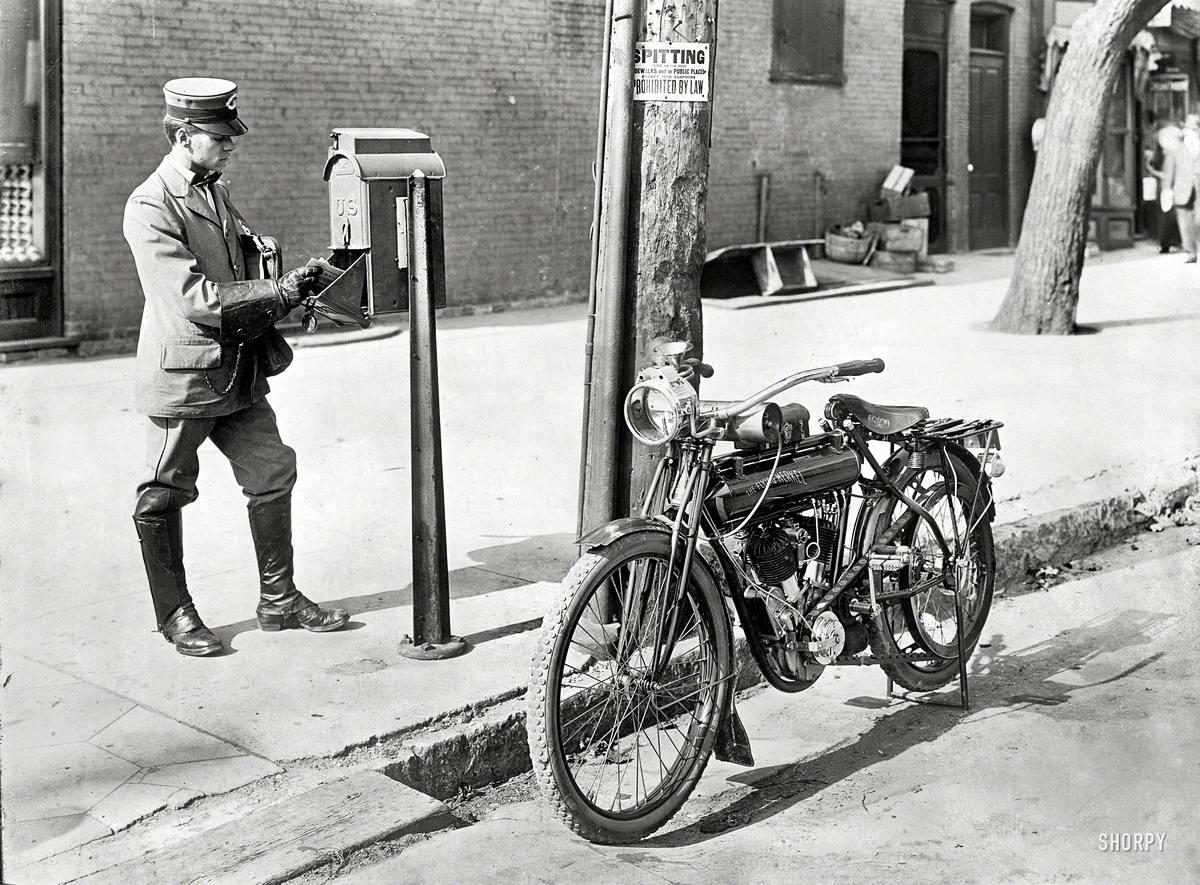 Почтальон со свои мотоциклом возле уличного почтового ящика (1915 год)