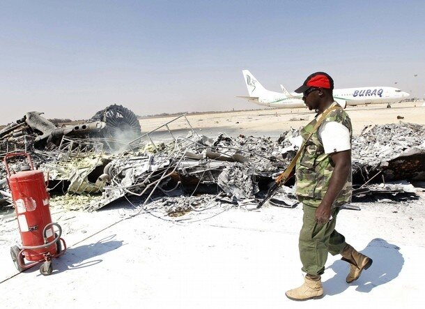A rebel fighter walks near an aircraft which was set on fire by forces loyal to Muammar Gaddafi during a fight at Tripoli Airport