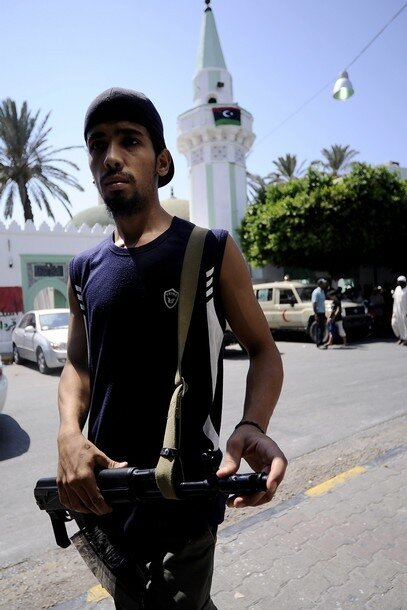 A Libyan rebel stands outside the Mayzar