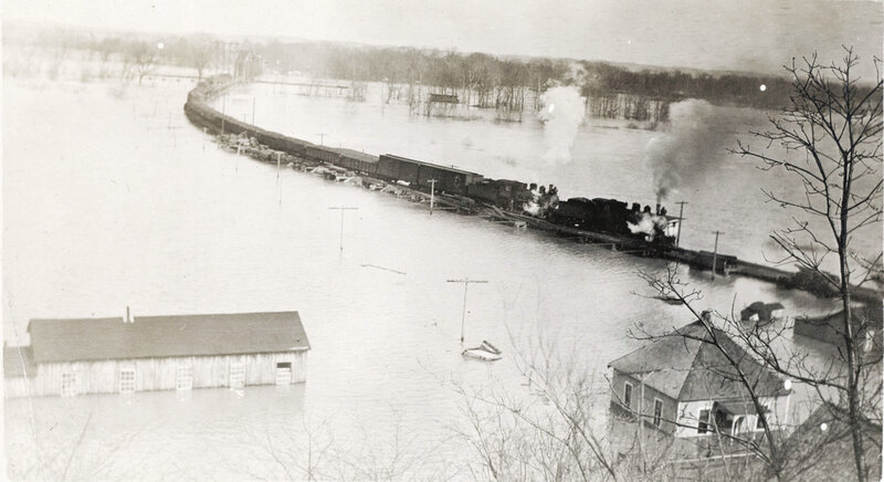 High water Illinois River at Valley City, Illinois. Locomotives make their way across the water on a bridge. 1913