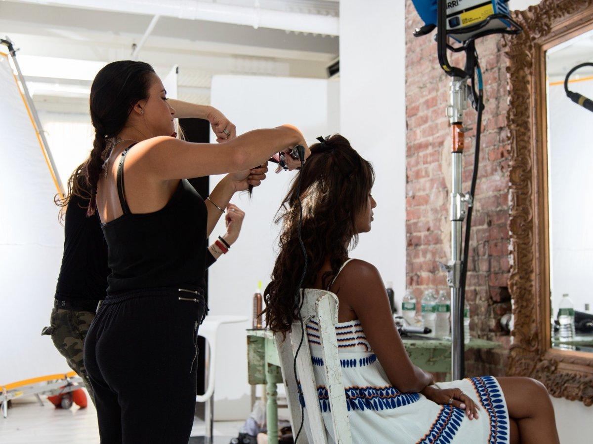 Модели Ванессе Фонсеке делают укладку перед фотосъемкой.