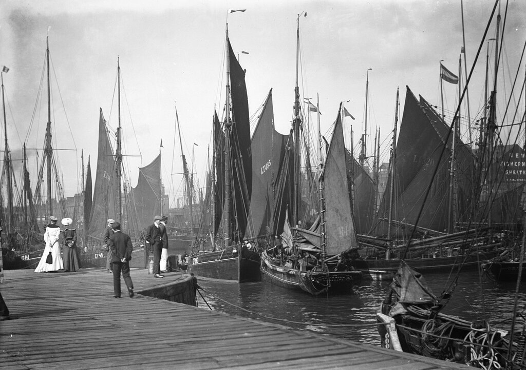 Men and women onlookers at the end of the quay looking at the forest of masts and sails in the harbour