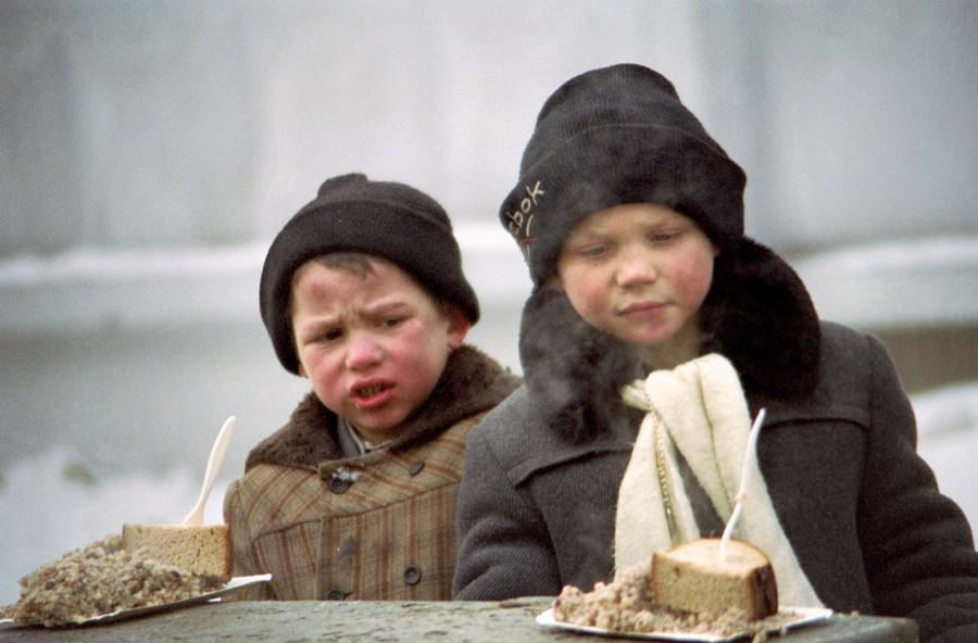 Бездомные мальчики получают благотворительную пищу
