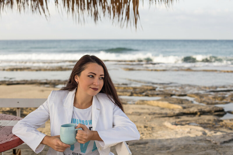 Female in white jacket holding a mug by the sea
