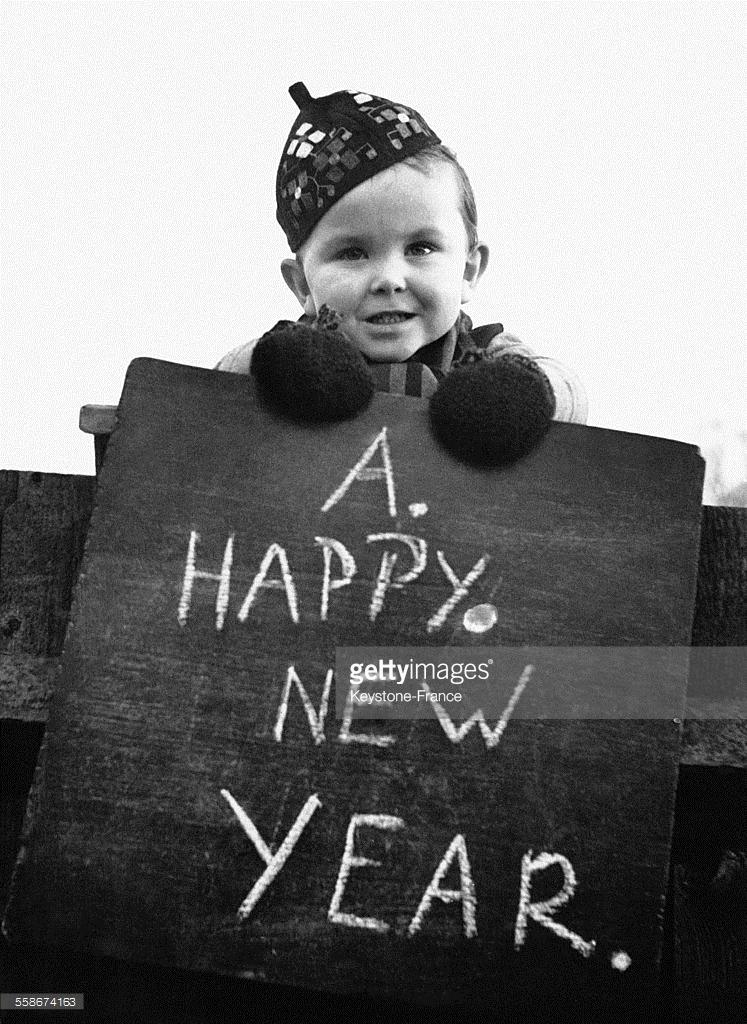 1948. Маленький ребенок несет дощечку, на котором он написал «С Новым годом» для своих соседей. 22 декабря