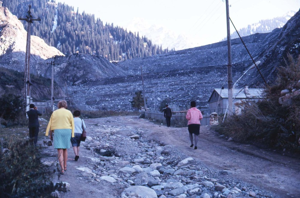 a group of people walking towards an earthen dam - They had built a large earthen dam. A waste of time. .JPG
