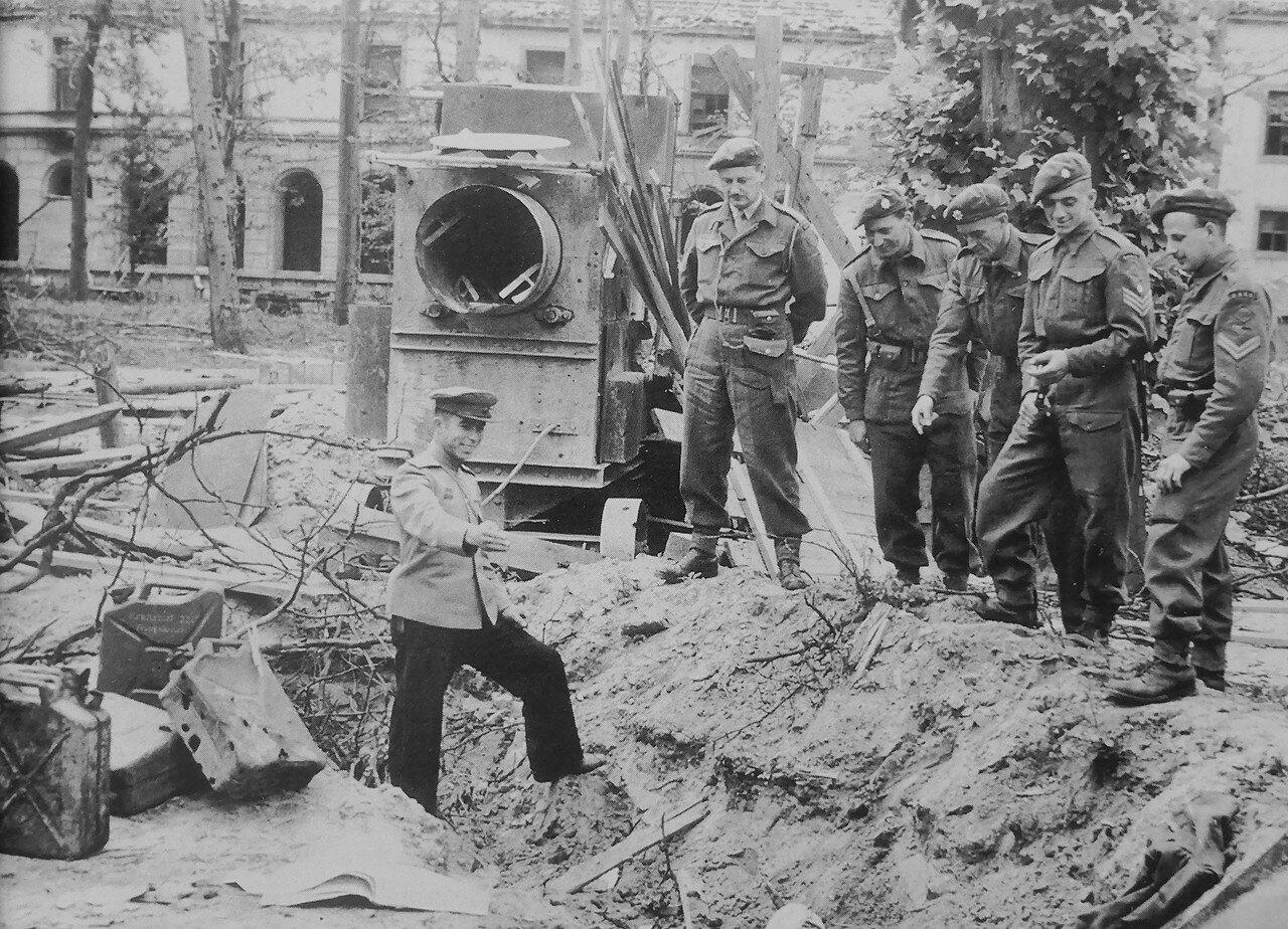 Советский офицер показывает британским военнослужащим место находки останков Гитлера.