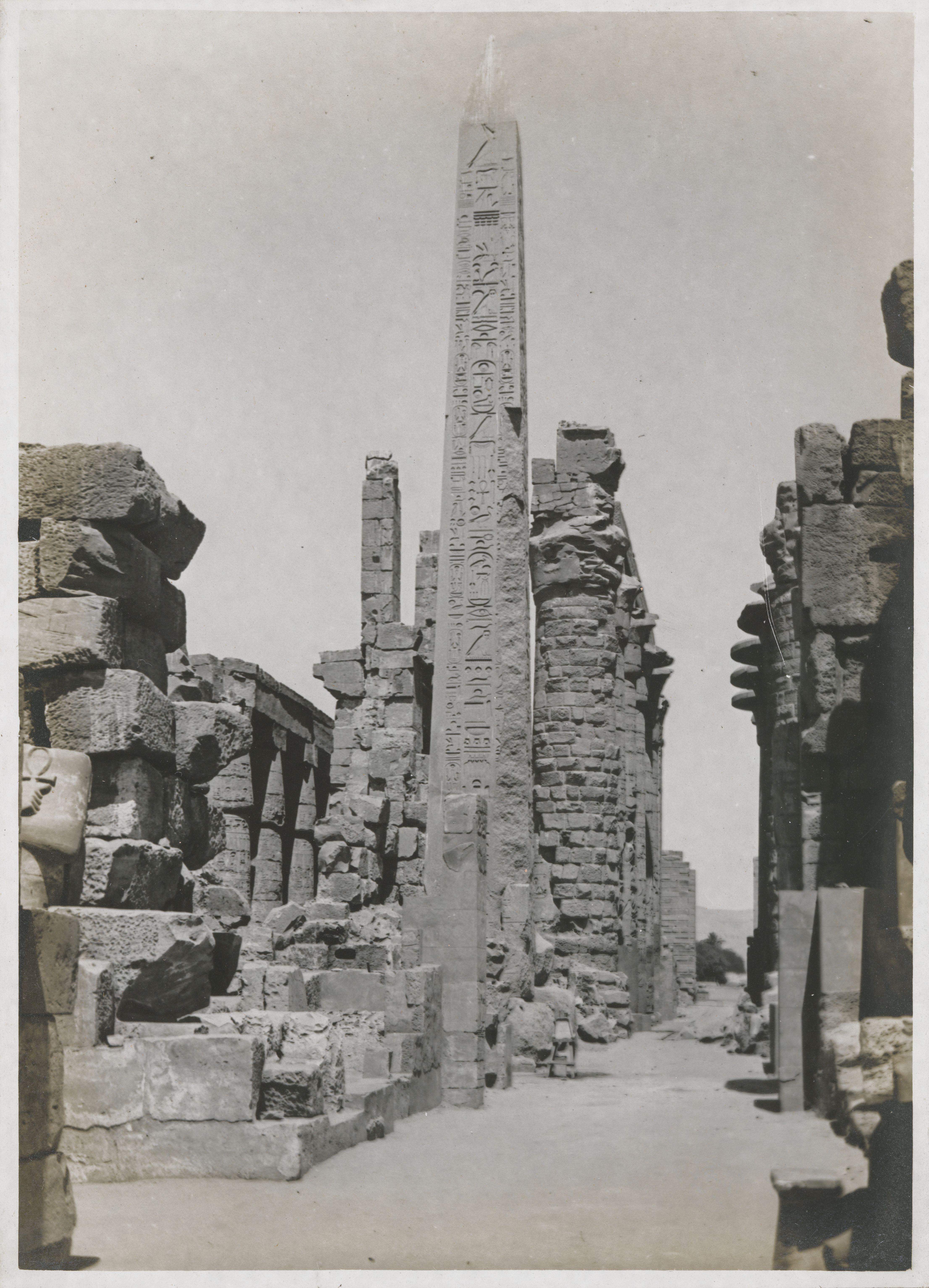 Карнак. Большой храм Амона.  Вид колонного зала от центрального двора. Обелиск из красного гранита высотой 23 м.