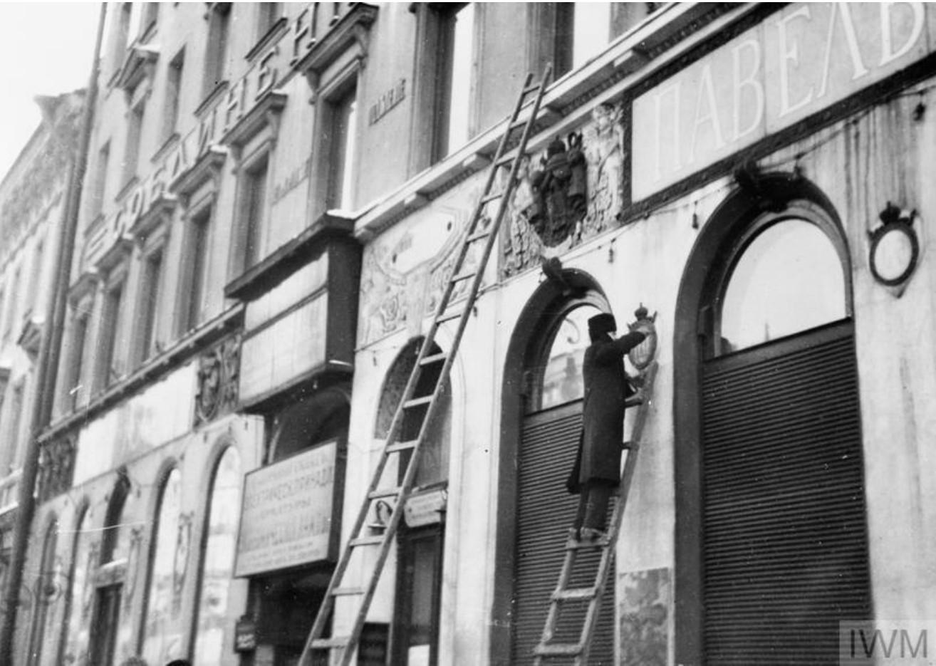 Революционеры сбивают символы царского режима с фасада официальных зданий, Петроград
