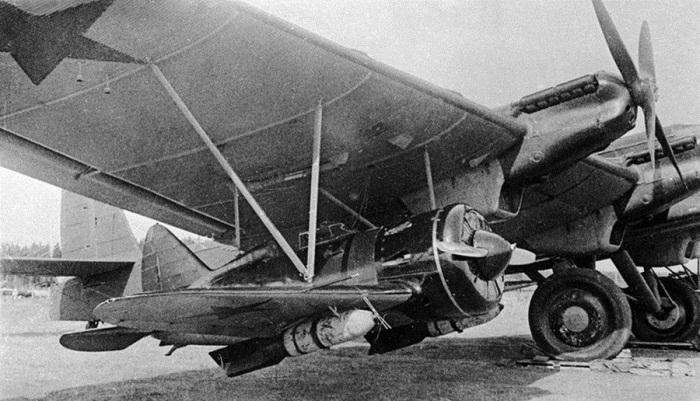 Под крылом самолета ТБ-3 подвешен истребитель И-16 с фугасными бомбами весом 250 кг каждая. Лето 194