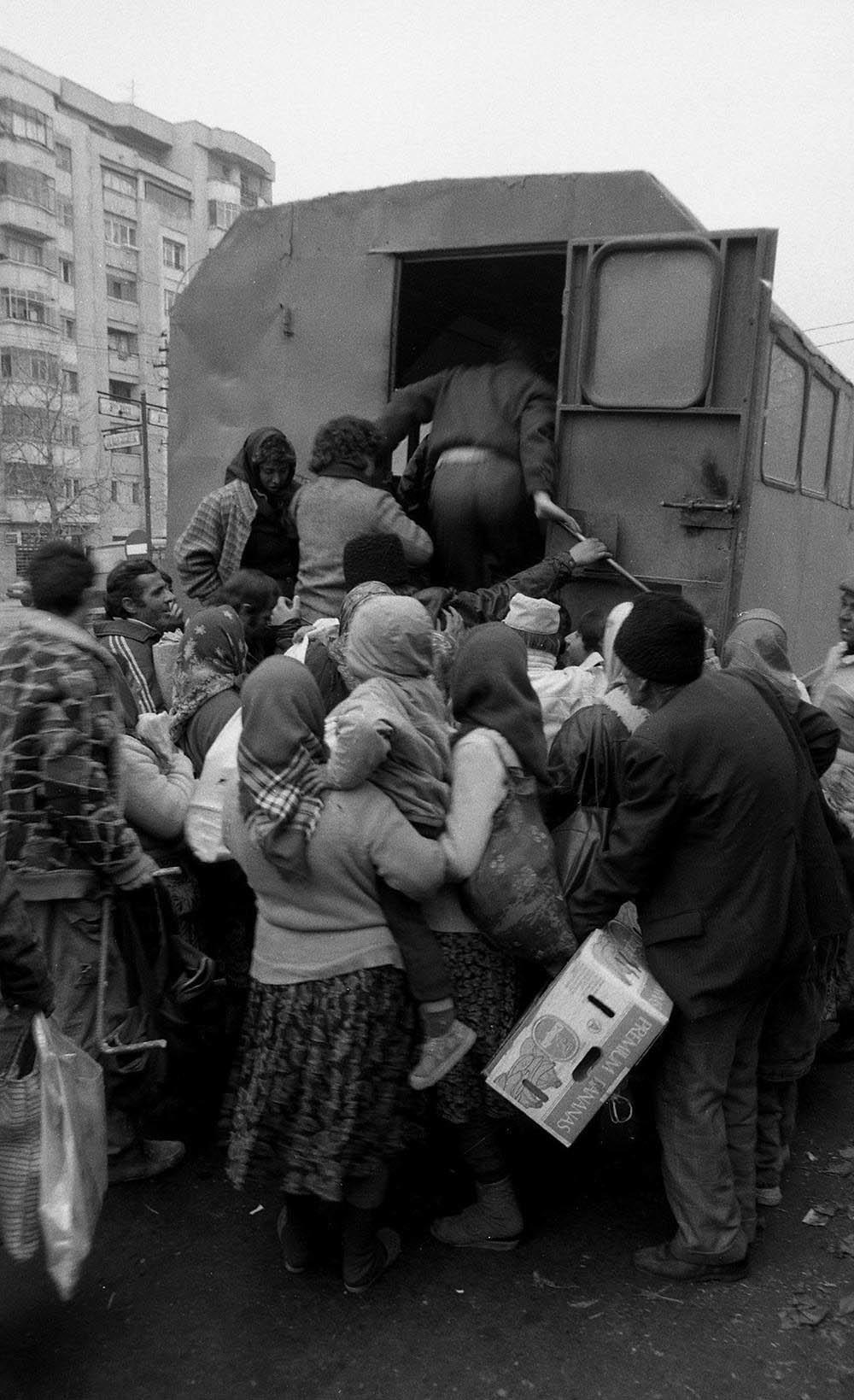 Люди забираются в грузовик, на котором перевозили пассажиров по городу. Сейчас эти грузовики использ