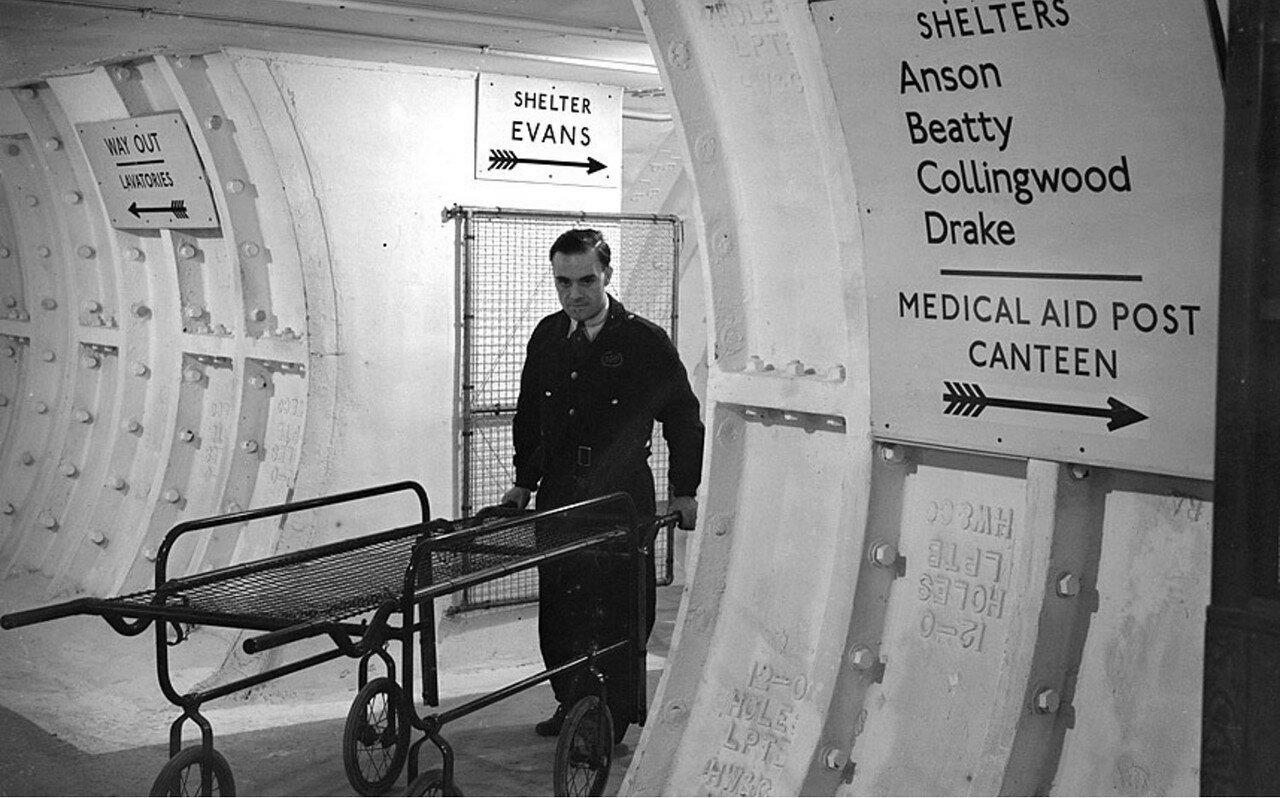 1942. Человек толкает носилки через одно из новых бомбоубежищ